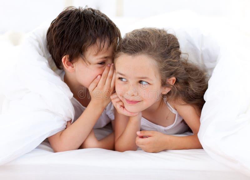 Siblings die op het bed van de ouder spelen stock afbeelding