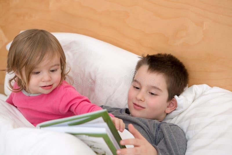 Siblings die samen lezen stock afbeeldingen