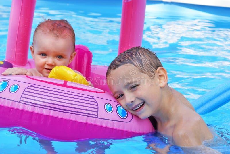 Siblings die van de Pool genieten stock foto