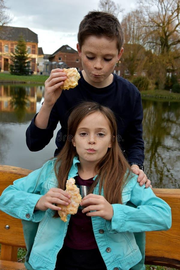 Siblings eating cake royalty free stock photos
