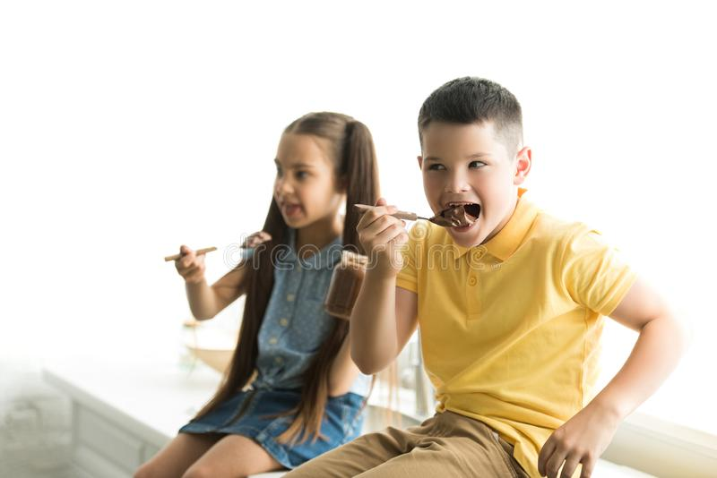 siblings eating chocolate together royalty free stock images