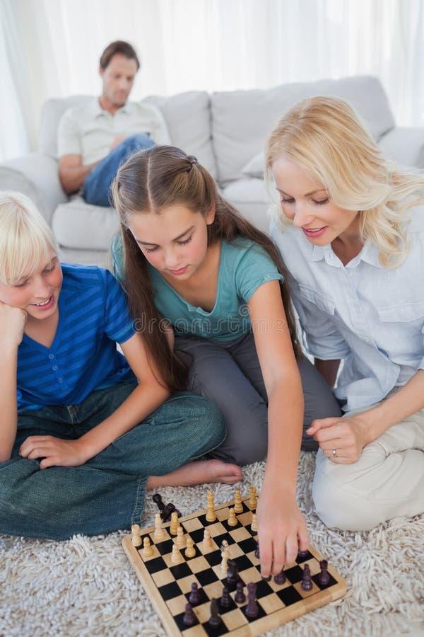 Siblings en moeder speelschaakzitting op een tapijt stock afbeelding