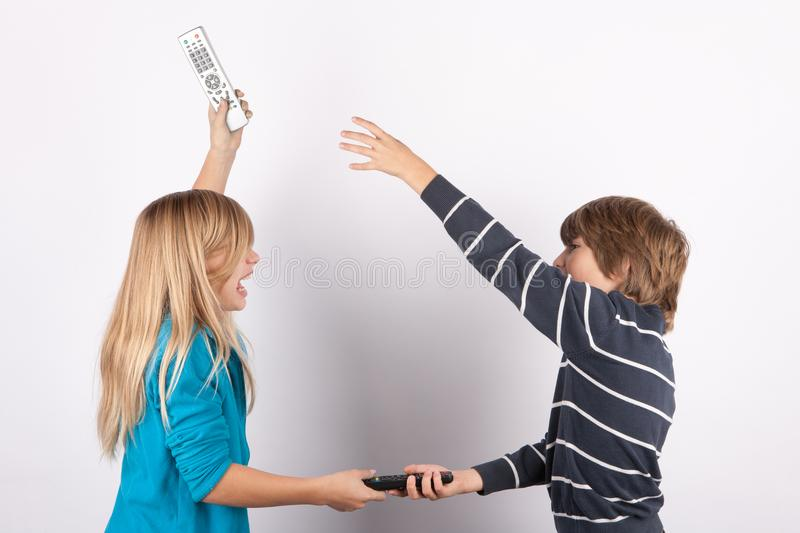 Siblings fighting for TV remote controls stock images