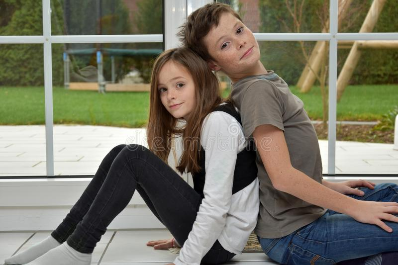 Siblings with freckles sitting back to back stock photography