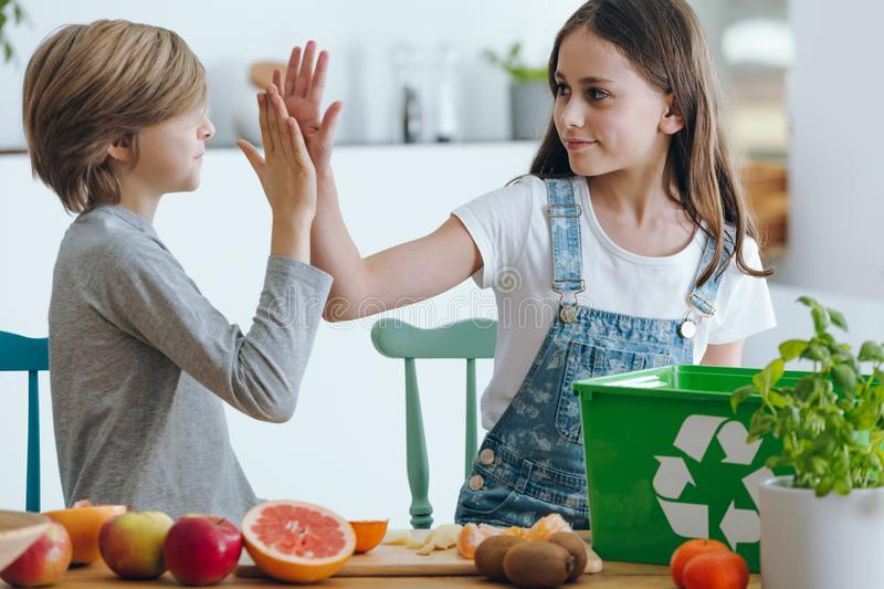 Siblings giving high five stock photo