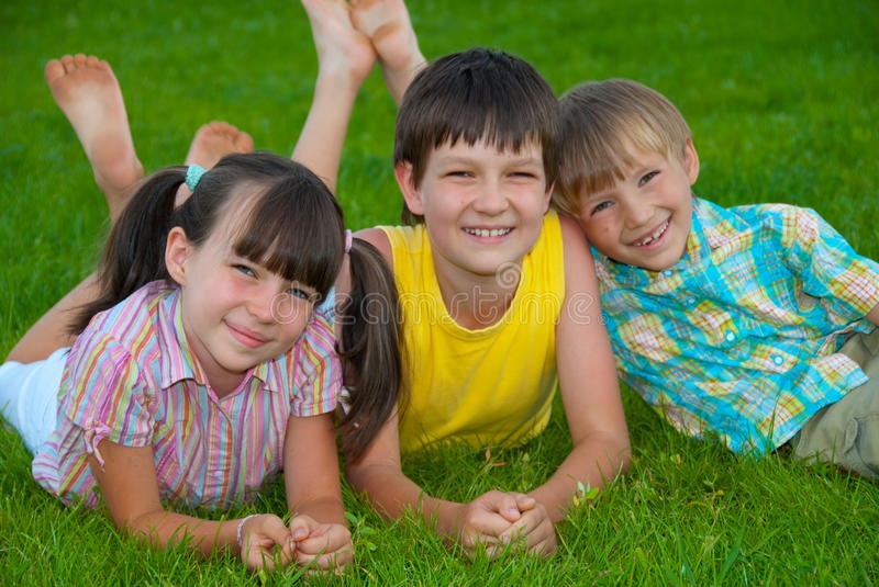 Siblings on grass. Three happy siblings sitting and lying on grass royalty free stock images