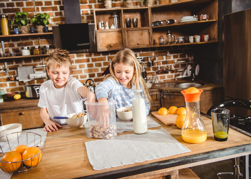 Siblings have breakfast. Brother and sister have corn flake rings for breakfast sitting at the table in kitchen royalty free stock photography