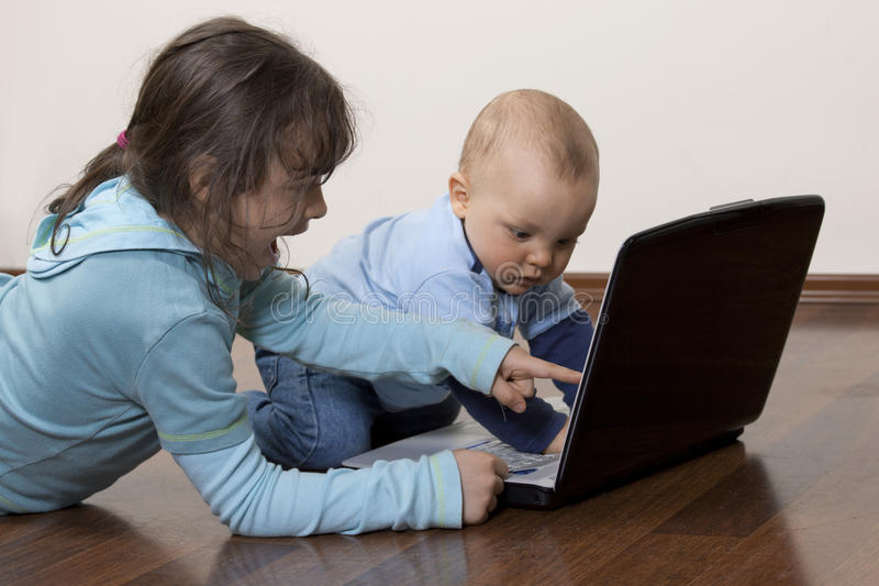 Siblings with laptop. On the floor stock photography