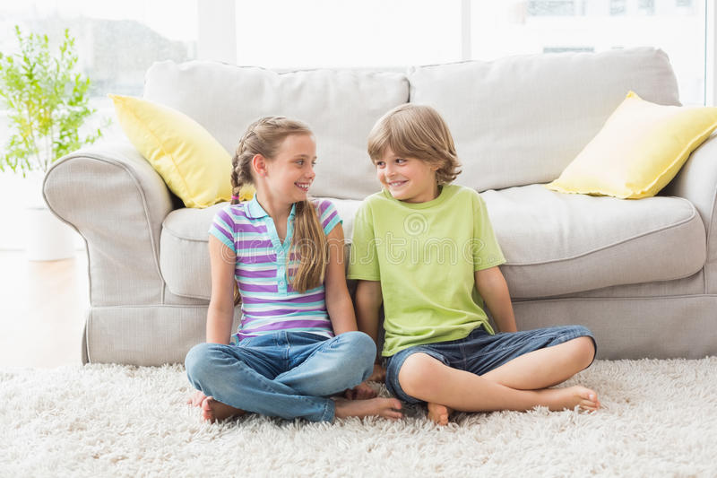 Siblings looking at each other while sitting in liviung room stock images
