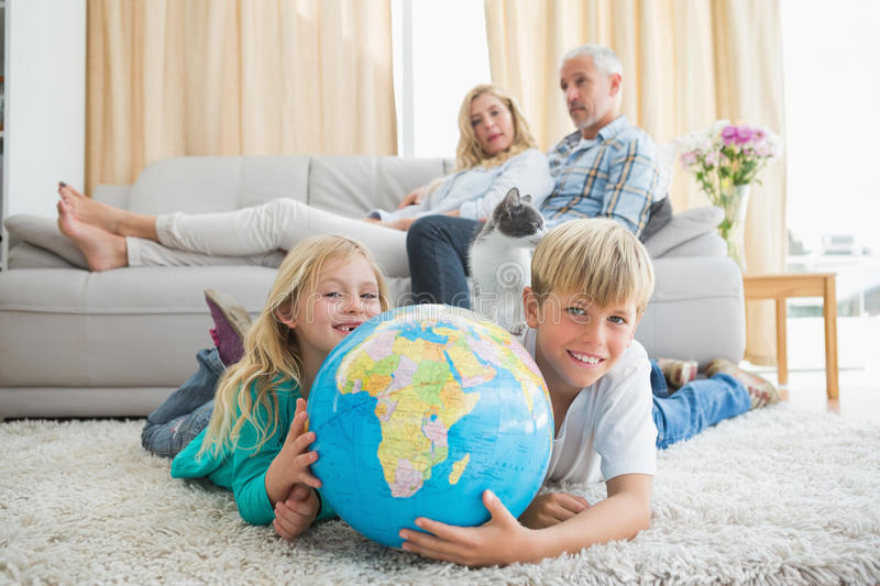Siblings looking at globe on the floor. At home in the living room stock image