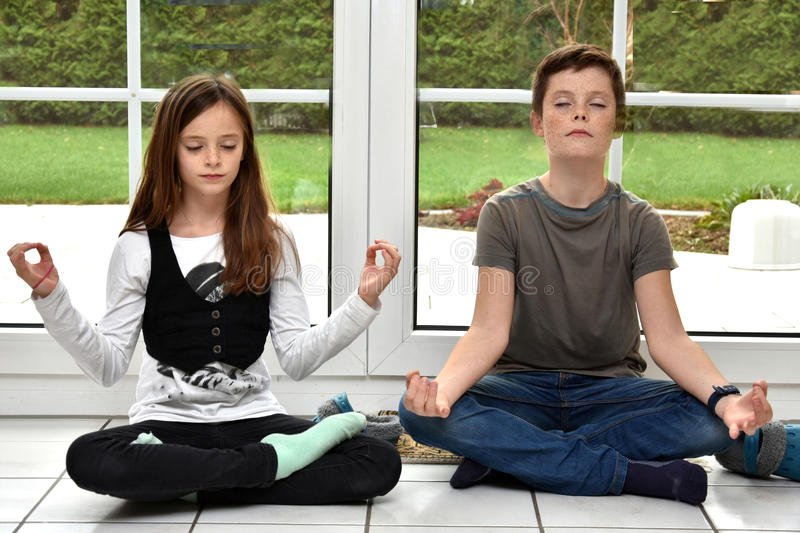 Siblings meditating stock photos
