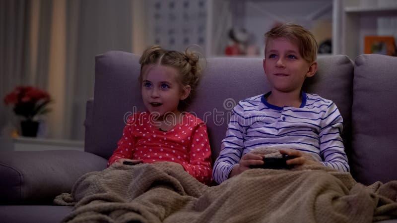 Siblings omvat met plaid die van videospelletje genieten, spelend bij nacht, die console gebruiken royalty-vrije stock fotografie