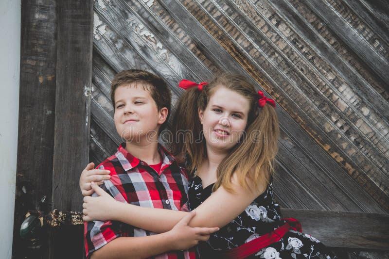 Siblings in ongemakkelijke omhelzing stock fotografie