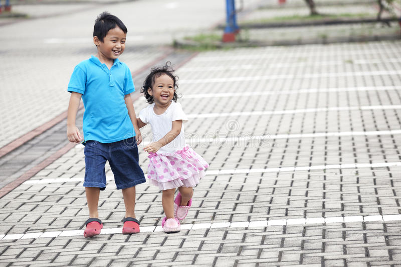 Siblings on parking lot. Happy asian siblings walking on parking lot shot outdoor royalty free stock images