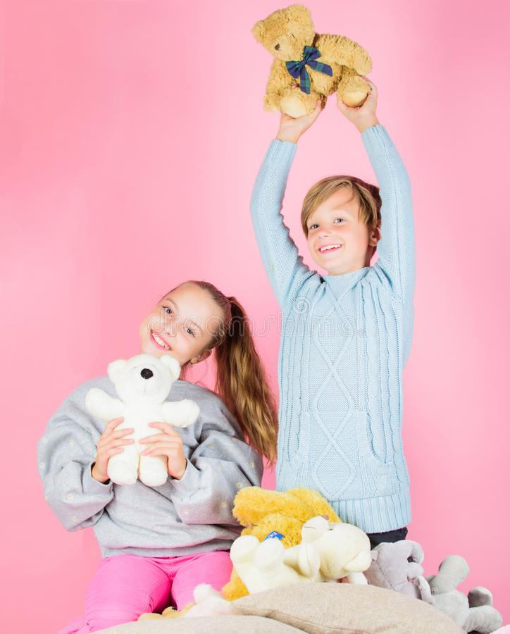 Siblings playful hold teddy bear plush toys. Boy and girl play with soft toys teddy bear on pink background. Bears toys royalty free stock photo