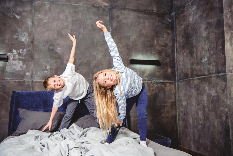 Siblings playing on bed. Cute smiling siblings in pajamas playing and exercising on bed royalty free stock photography