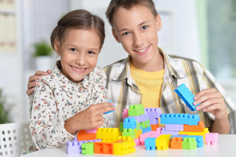 Siblings playing lego stock photos