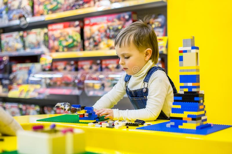 Siblings playing lego. On a yellow background royalty free stock photography