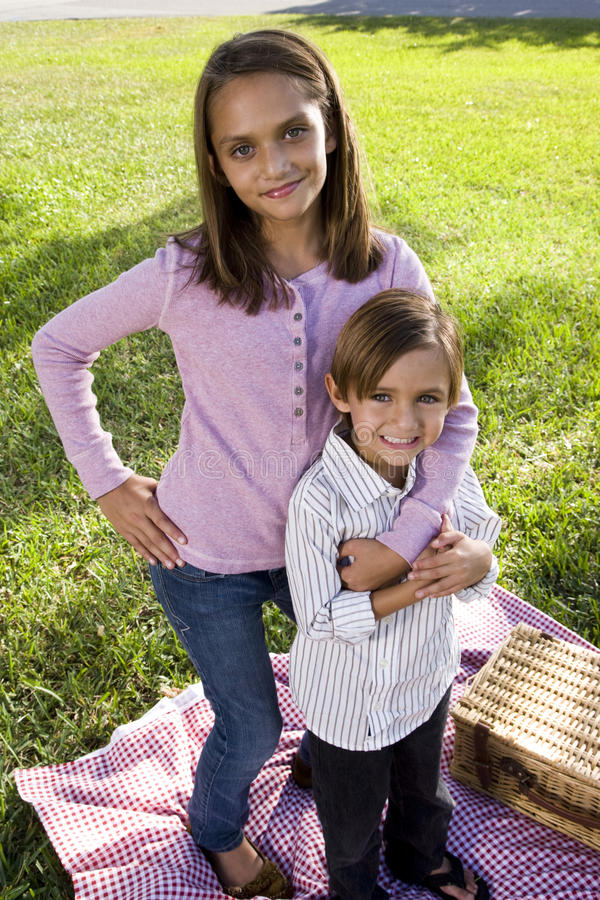 Download Siblings Posing For Camera Having Picnic In Park Stock Photo - Image: 12696056