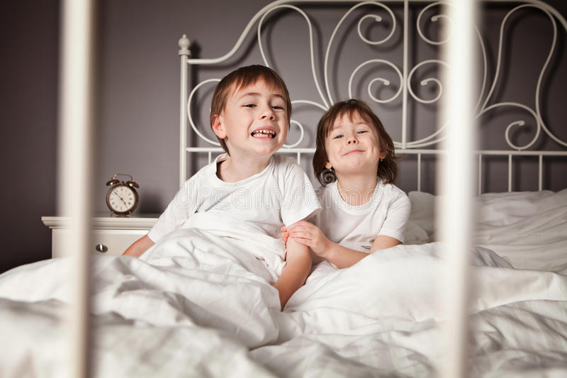 Siblings pulling faces. Brother and Sister in their parents bed pulling funny faces stock photography