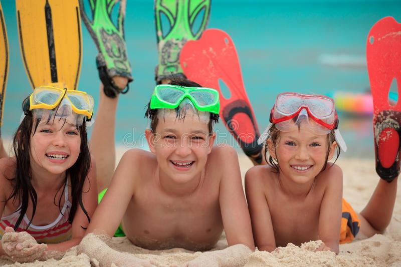 Siblings ready for snorkeling. Three siblings wearing snorkeling flippers and goggles lay on the beach together stock images