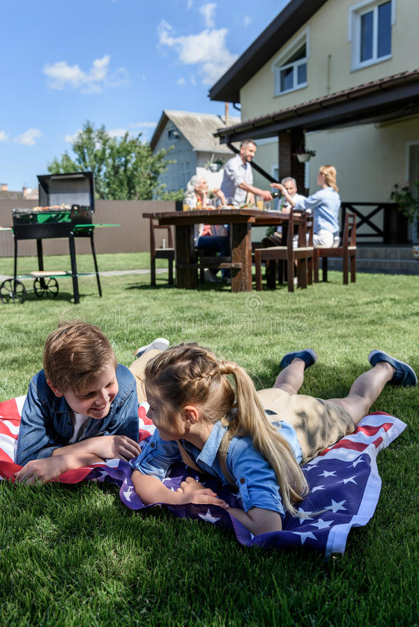 Siblings resting on american flag with family having picnic behind. Little siblings resting on american flag with family having picnic behind royalty free stock photos