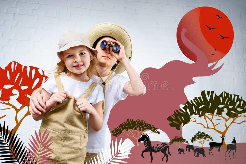 siblings in safari costumes hugging and looking in binoculars at zebra, elephants royalty free stock photos