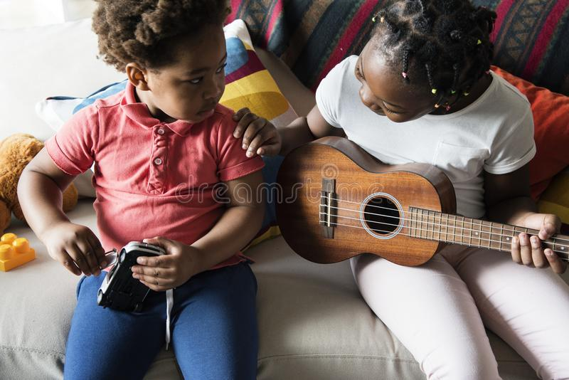 Siblings spending time together playing guitar stock images