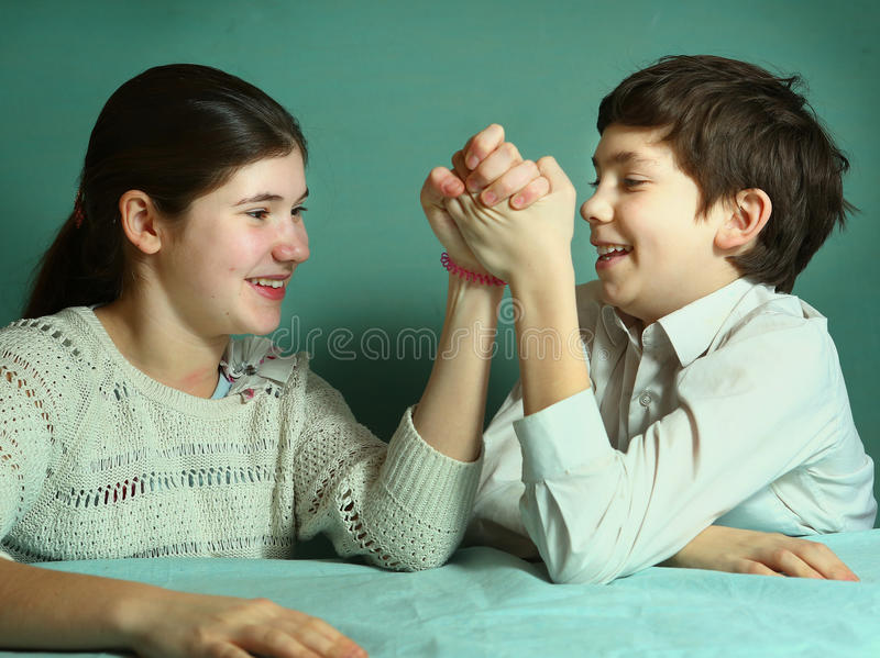 Siblings teenager brother and sister compete arm wrestling. Siblings teenager brother and sister arm wrestling close up smiling photo royalty free stock photos