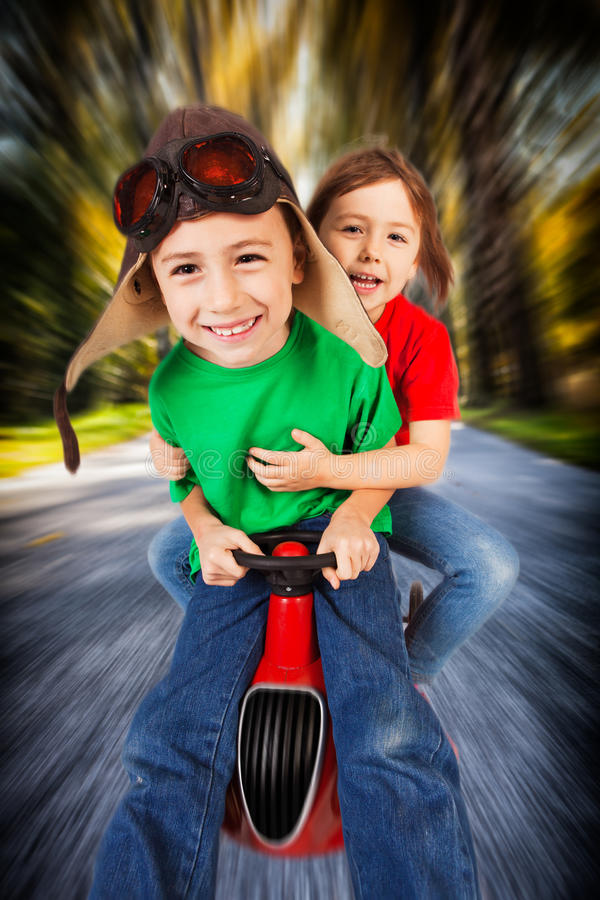 Siblings on toy racing car. Siblings in retro racing hat and goggles driving on toy car at speed with blurred background stock photography