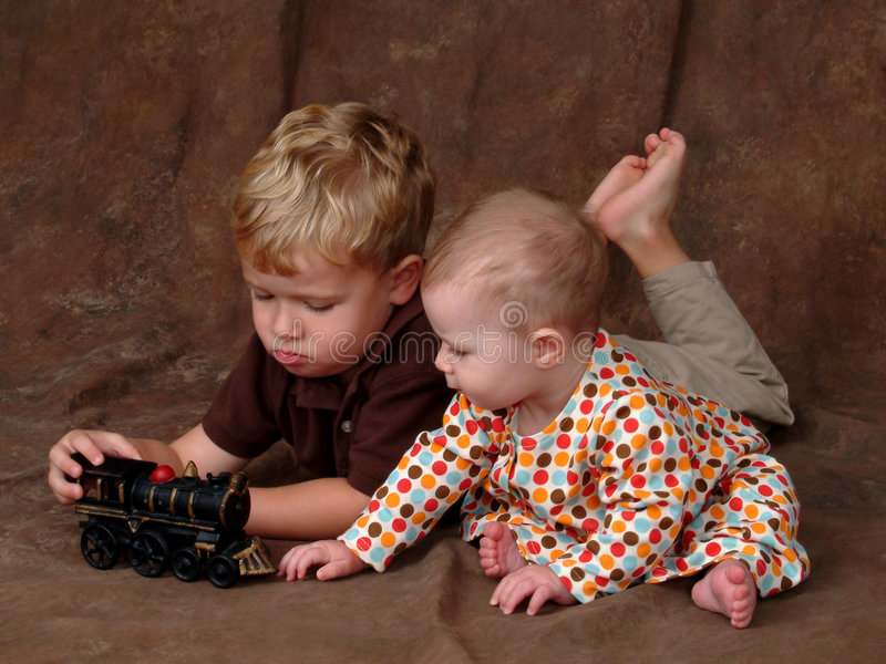 Siblings with Toy Train. Baby in sitting position and boy laying on his belly looking at toy train royalty free stock photography