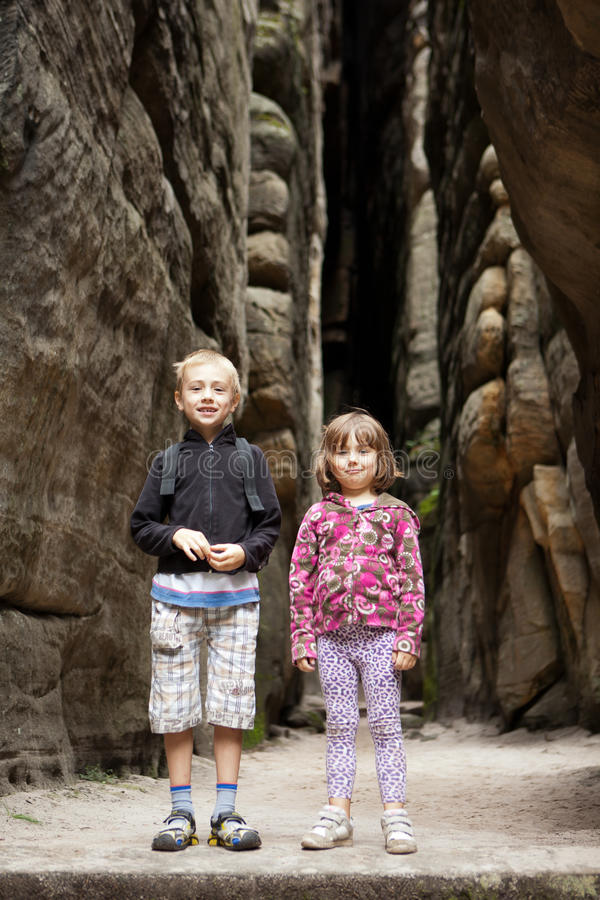 Siblings on trip. Young brother and sister standing happy and relaxed beside a vertical rock face while on trip stock photography