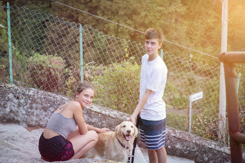 Siblings walking with a dog. Two smiling siblings walking with a dog royalty free stock photos