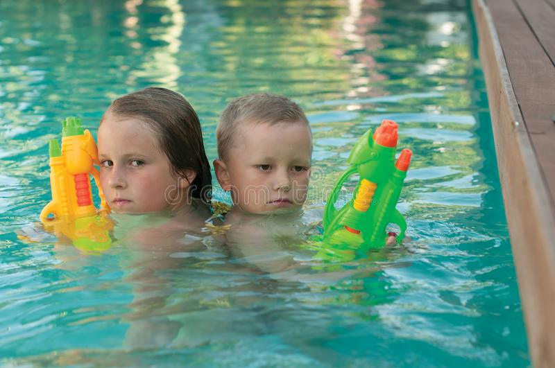 The siblings with a water pistols playing in a pool stock photos