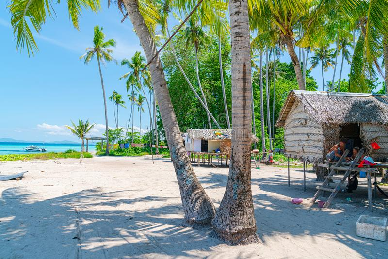 Thatch stilt homes on idyllic tropical beach royalty free stock photo