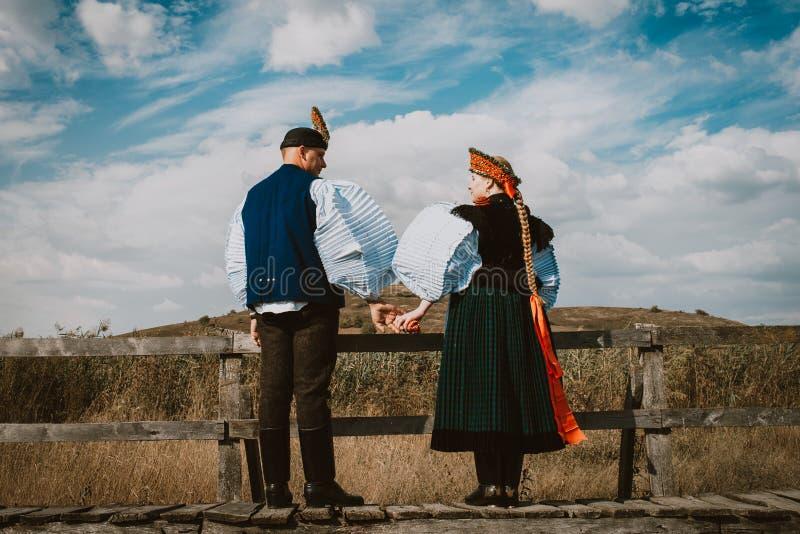Sic Transilvania Roemenië 09 08 2018 Bruid en bruidegom in traditioneel kostuum bij hun huwelijksdag het springen royalty-vrije stock foto's