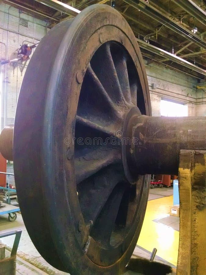 Sich fortbewegendes Metallantriebsrad in Reparaturwerkstatt lizenzfreies stockbild