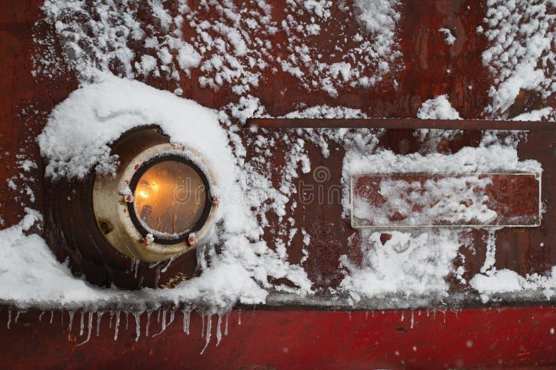 Sich fortbewegendes Zugdetail mit den Scheinwerfern bedeckt im Schnee lizenzfreie stockfotos