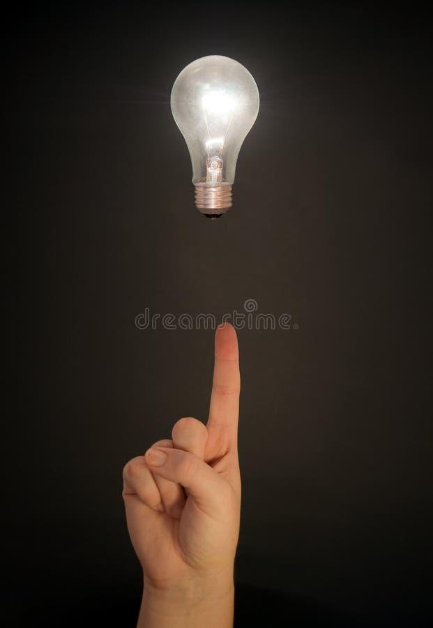 Sich hin- und herbewegende Glühlampe und Hand lizenzfreies stockfoto