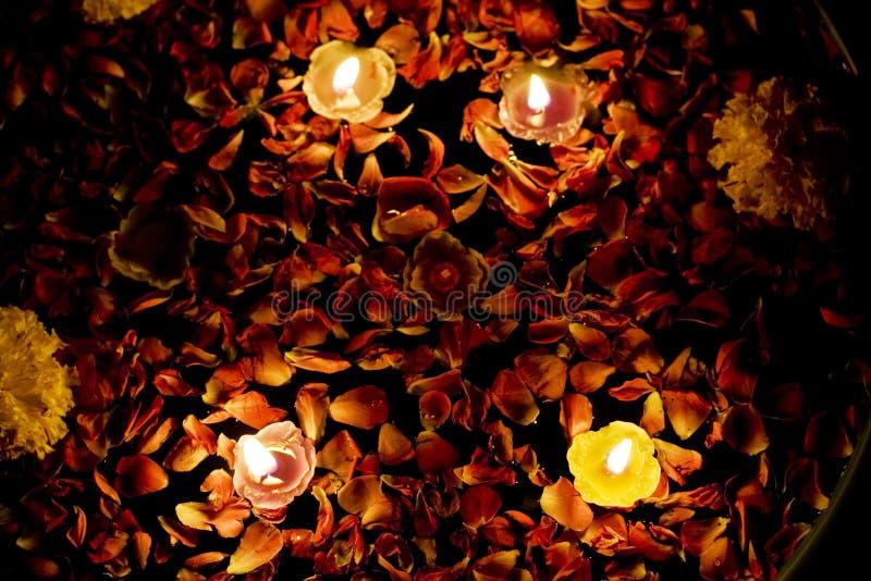 Sich hin- und herbewegende Kerzen im Rosen-Wasser mit Ringelblume lizenzfreie stockbilder
