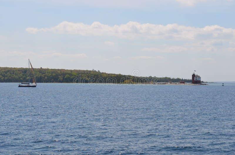 Sich hin- und herbewegender Leuchtturm und Segelboot lizenzfreie stockbilder