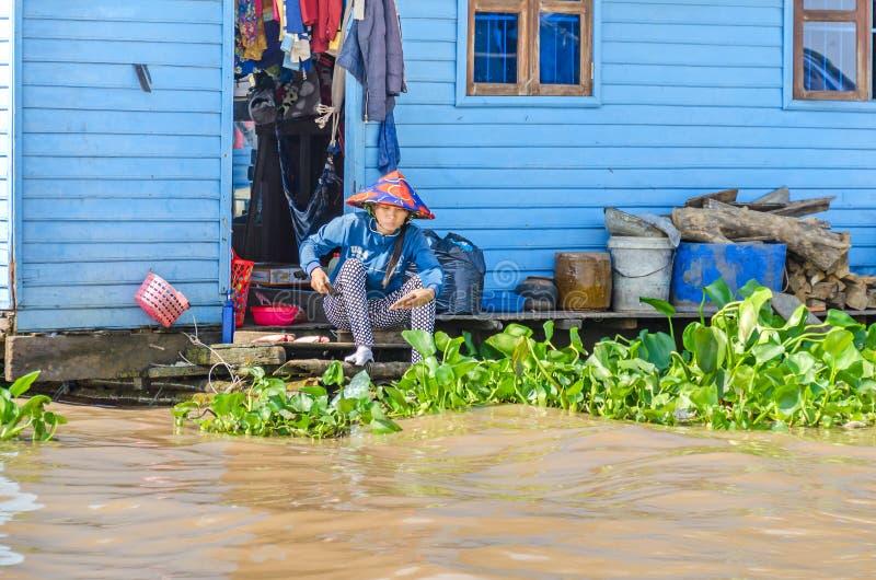 Sich hin- und herbewegendes Dorf auf dem Tonle schwächen See in Kambodscha und in einer Frau lizenzfreie stockfotografie