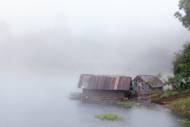 Sich hin- und herbewegendes Flosshaus auf Fluss mit nebeligem Hintergrund lizenzfreie stockbilder