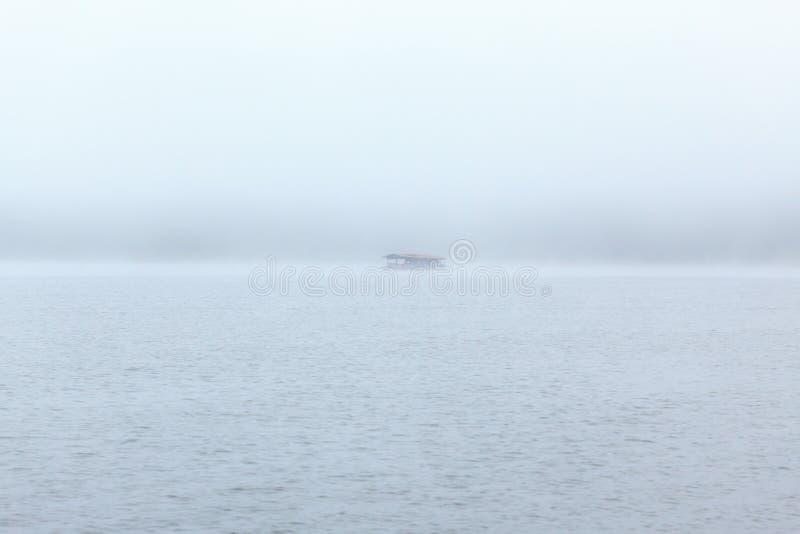 Sich hin- und herbewegendes Flosshaus auf Fluss mit nebeligem Hintergrund stockbild