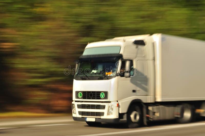 Sich schnell bewegender weißer LKW stockfotografie