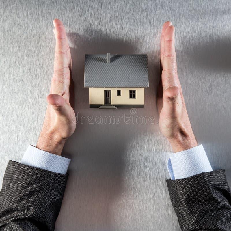 Sicheres Hauptkonzept mit geradem Geschäftsmann übergibt schützendes neues Haus stockfotografie