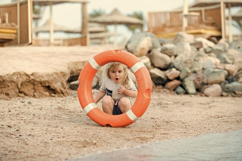 Sicherheit auf dem Strand Jungenkind, das mit Lebensretter spielt stockbilder