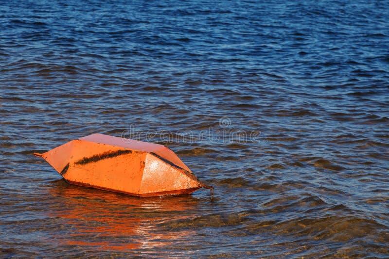 Sicherheit auf dem Wasser Eine große orange Boje liegt horizontal nahe dem Ufer auf dem Wasser der Bucht des Flusses stockfotos