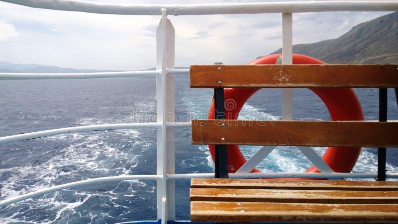 Sicherheit auf einem Passagierschiff: eine Bank und eine Rettungsleine Sichtbare Spur des Segelschiffs und der Berge im Abstand stockfotos