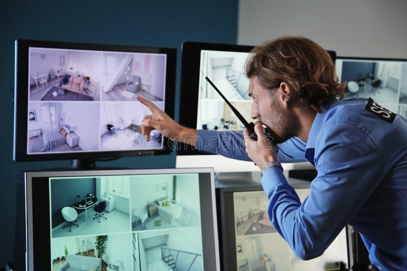 Sicherheitsbeamteüberwachung moderne Überwachungskameras im Überwachungsraum stockbild